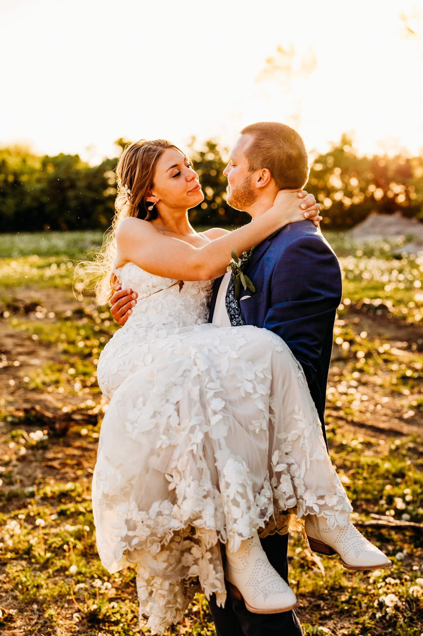 Groom holds his bride and she looks into her eyes outside at their Schroeder Farm wedding