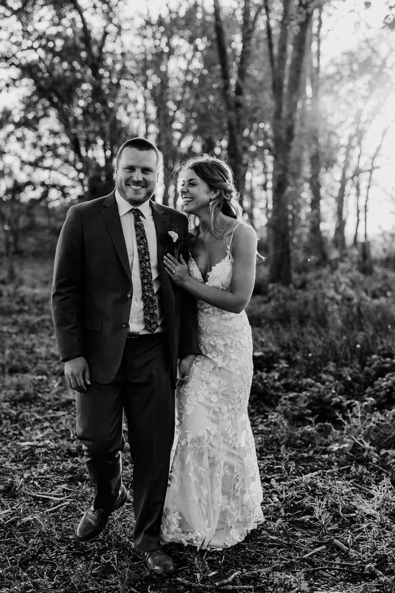 Couples smiles at each other outside at their Schroeder Farm wedding in black and white portraits
