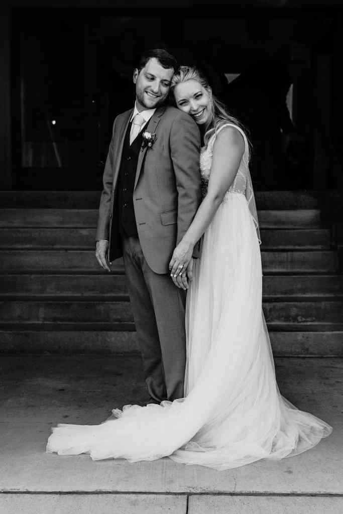 Bride stand behind groom and lays her cheek on his shoulder in black and white portrait at their Duluth Malting Building wedding