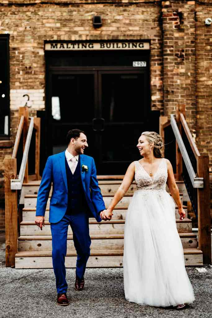 Couples smiles at each other outside at their Duluth Malting Building Wedding