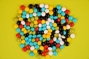 Colorful candies isolated on green background stock photo