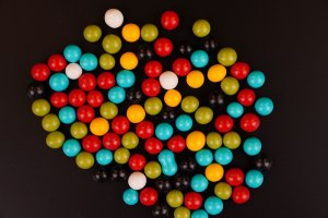 Multicolored round dragee candies on black background