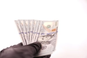 Black Leather Gloves Holding Money