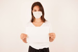 Girl in medical mask holding sign