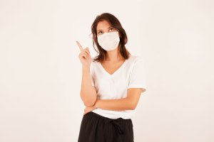 Girl in medical mask thinking about an idea