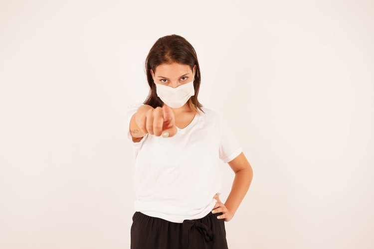 Woman in medical mask pointing finger at you