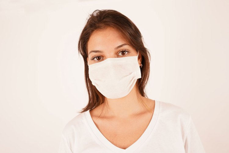 Woman with brown hair wearing a surgical mask