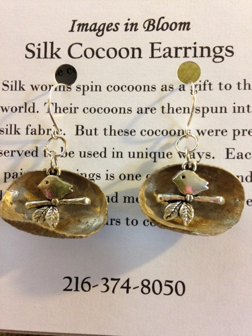 half cocoons, painted platinum with a charm of a bird suspended in the cup form of the cocoon.