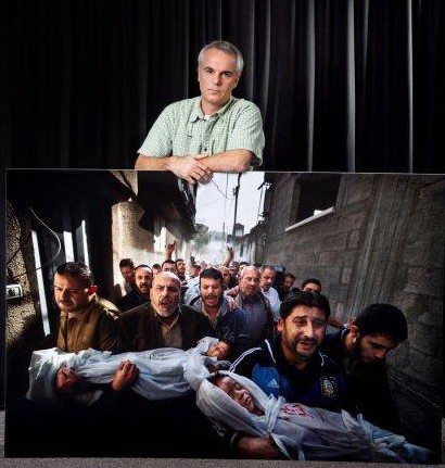 "Paul Hansen, reporter du journal suédois Dagens Nyheter, photographié avec un tirage grand format d'""Un enterrement à Gaza"" (2012), premier prix du World Press Photo 2013."