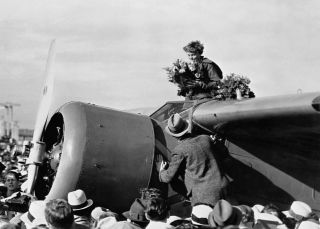 Amelia Earhart is showered with flowers-the first person to successfully fly from Hawaii to California-NatlGeographic