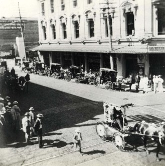 The decorated buggy in foreground indicates a parade in progress in Honolulu, street unknown.