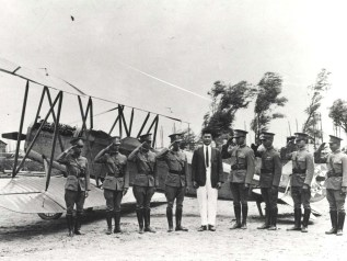 1st Hawaii resident to earn a pilot's license, stands with Chinese fliers & first airplane manufactured in China. The Honolulu born son of wealthy Chinese, Young soloed at Curtiss Flying School in Buffalo, NY on 10-2-1916. He later worked for Dr Sun Yat-Sen.