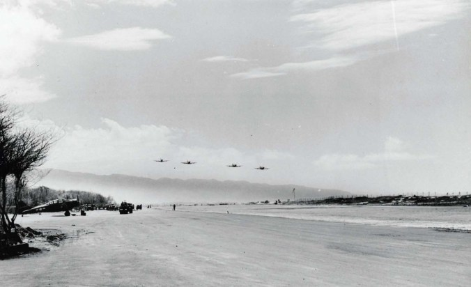 4 Bell P-39s fly over Haleiwa Field as maintenance work progresses at left.