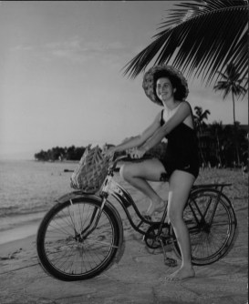 Francine King wearing a coconut hat with a coconut market basket on her bicycle-PP-32-7-026-1935