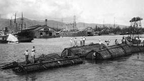 Harbor scene as the pontoons used to raise the F-4 (SS-23) pass by-(navsource-org)