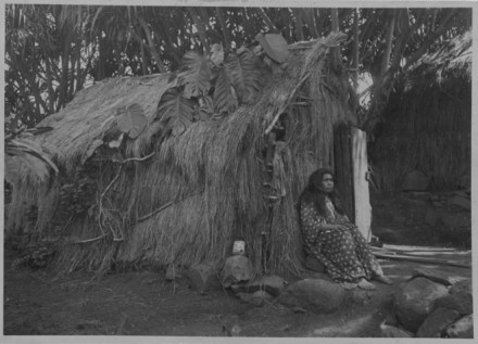 Hawaiian woman seated in front of a grass house, Halawa, Molokai-Baker-PP-32-3-010