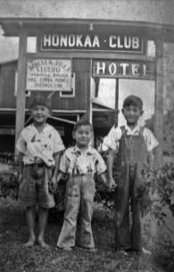 Hotel-Honokaa-Club-Alex, Robert, and Henry Morita standing in front of the Hotel Honokaa Club sign