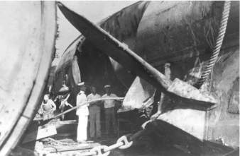 Naval personnel examine the large implosion hole in F-4's (SS-23) port side, in drydock at Honolulu-(navsource-org)-1915