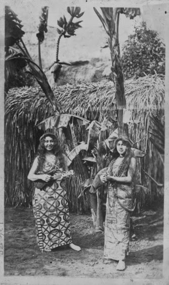 Two hula dancers with ukulele, wearing tapa outfits, Lalani Village-PP-32-10-007