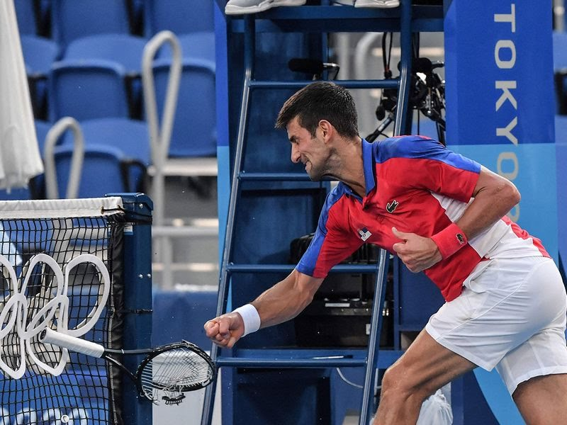Novak Djokovic smashes his racket in the bronze medal match against  Pablo Carreno Busta