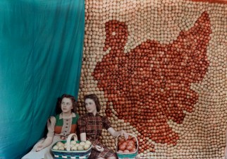 Two girls sit in front of an apple display in the shape of a turkey in West Virginia, 1939.