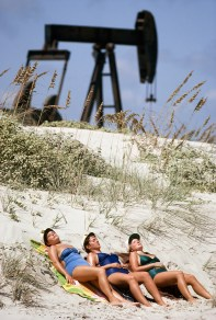 Women bask in the sun beside oil pumps, Padre Island, Texas. April 1980.