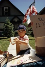 A boy sells lemonade from his front yard stand on Main Street in Aspen, Colorado, 1973.
