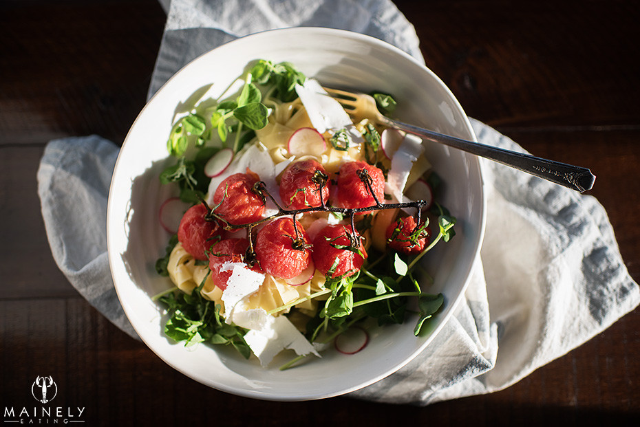 Light summer pasta with blistered cherry tomatoes, pea shoots and ricotta salata in a lemony broth