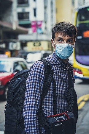 Man wearing a medical mask carries a camera and backpack across a city street.