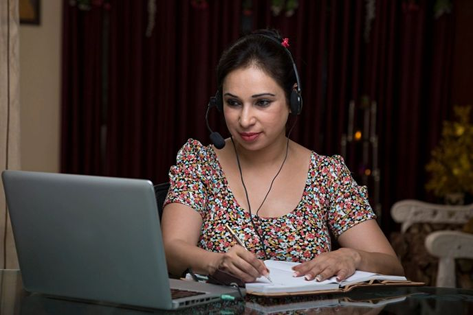 A woman wearing headphones works at a computer while writing in a notebook.