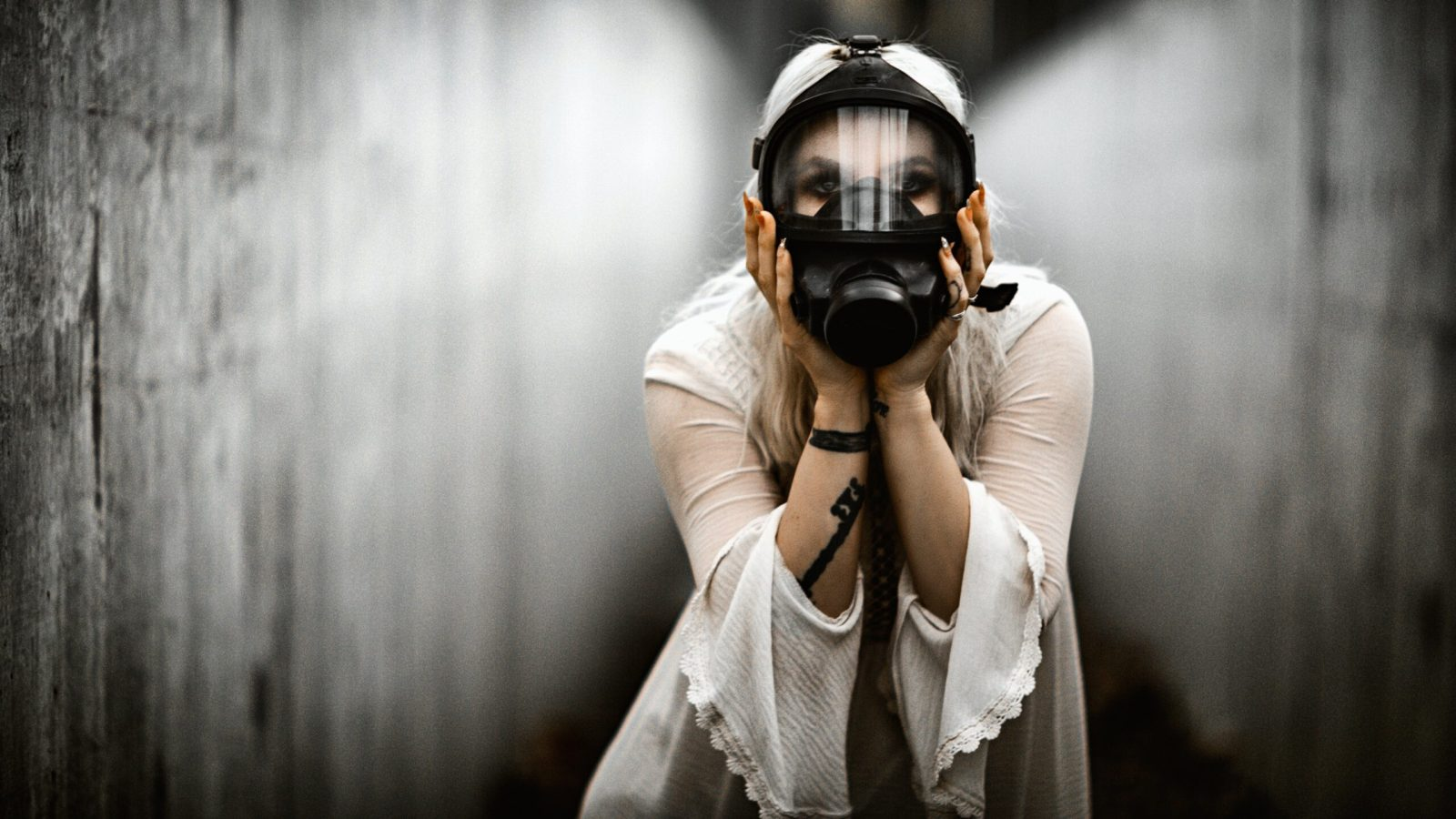 A woman in a long-sleeved white shirt wears a gas mask