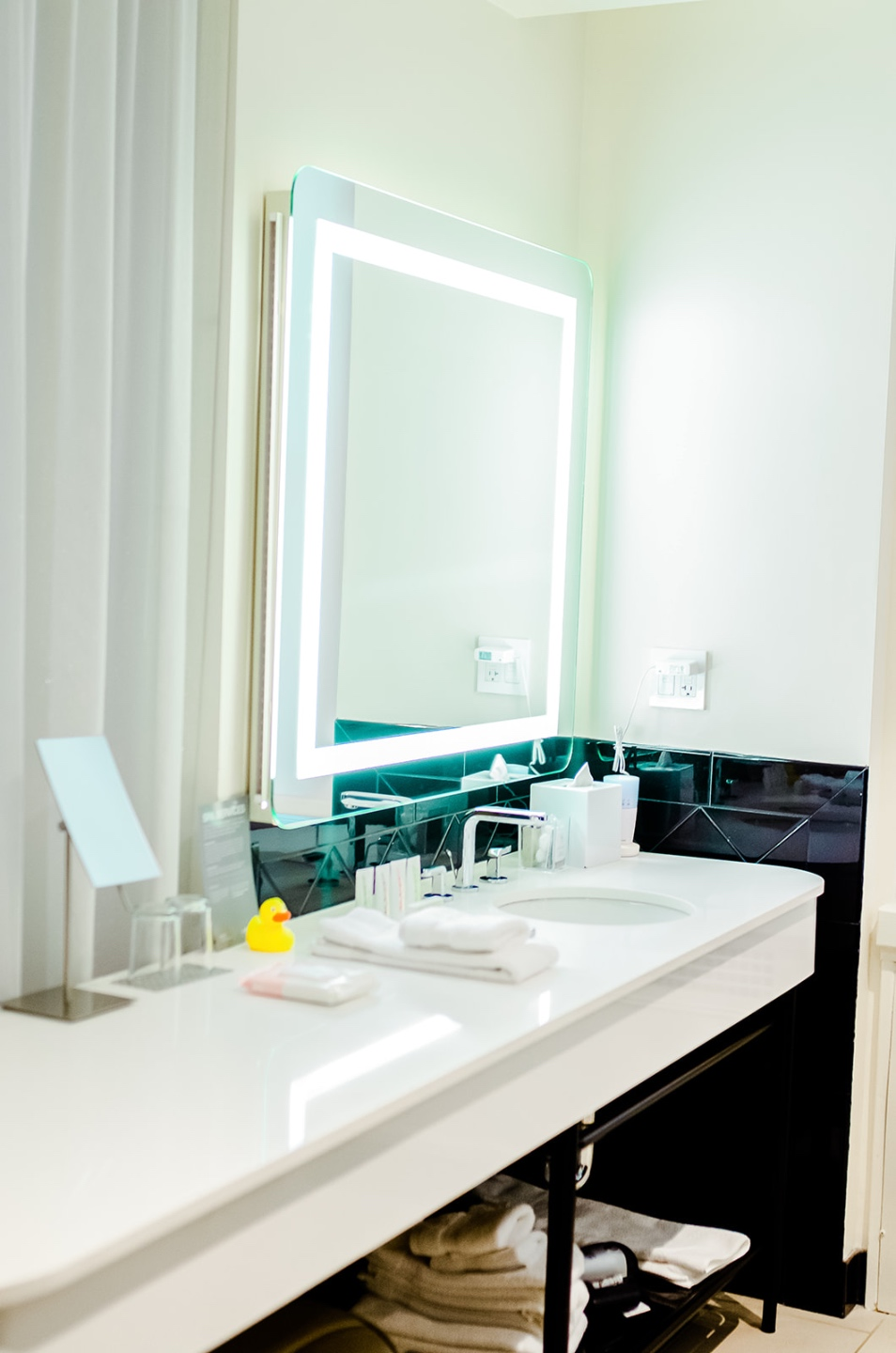 23 Awesome Things To Do in Durham - I'm Fixin' To - @imfixintoblog | Things to do in Durham by popular NC travel blog, I'm Fixin' To: image of a 21c Museum hotel bathroom with a lighted mirror, white vanity, and black tile walls.
