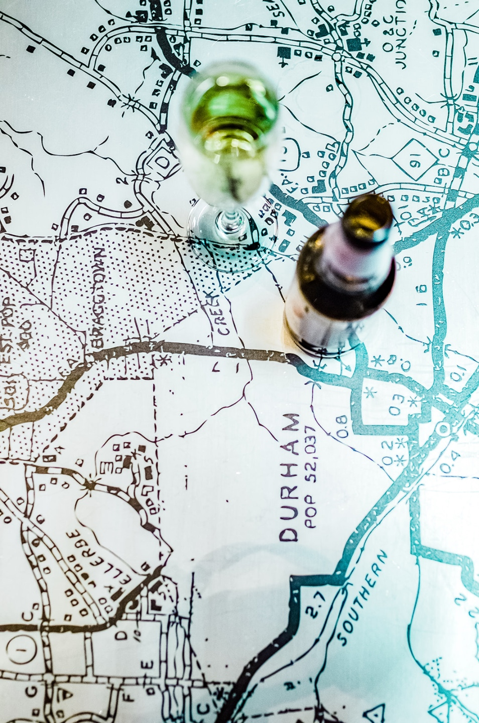 23 Awesome Things To Do in Durham - I'm Fixin' To - @imfixintoblog | Things to do in Durham by popular NC travel blog, I'm Fixin' To: image of a bottle of beer resting on a table covered with a black and white map of Durham.