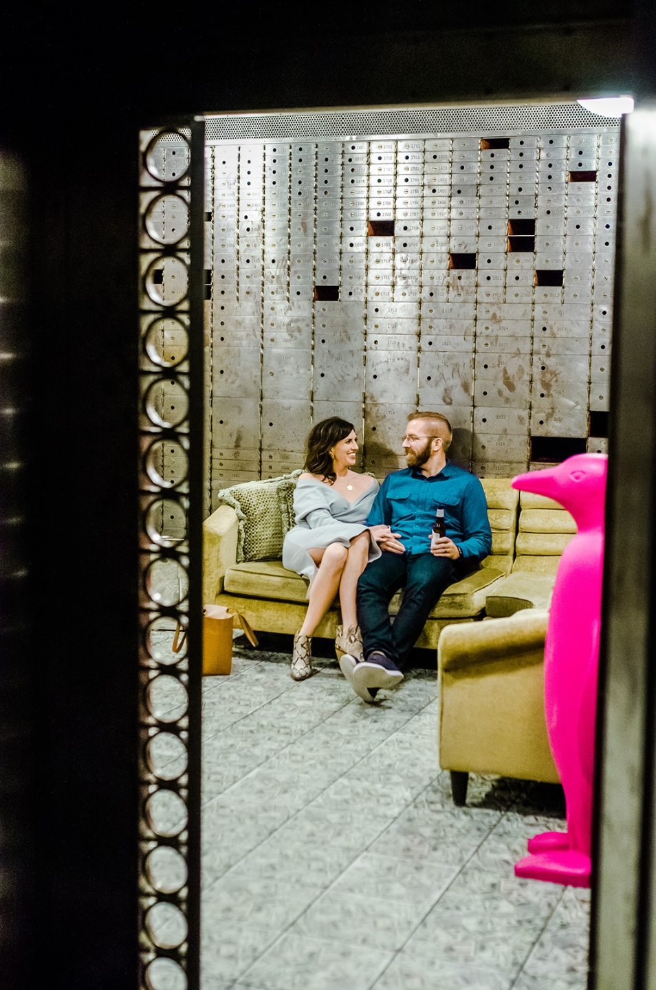23 Awesome Things To Do in Durham - I'm Fixin' To - @imfixintoblog | Things to do in Durham by popular NC travel blog, I'm Fixin' To: image of a man and woman sitting together in a old bank vault on a gold velvet sectional couch.
