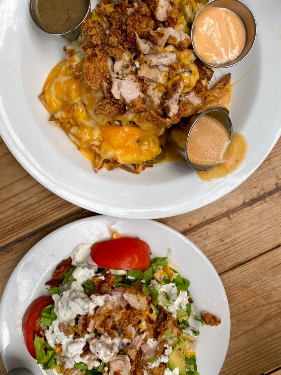 23 Awesome Things To Do in Durham - I'm Fixin' To - @imfixintoblog | Things to do in Durham by popular NC travel blog, I'm Fixin' To: image of cheese fries and a salad with tomatoes, bacon, and blue cheese dressing.