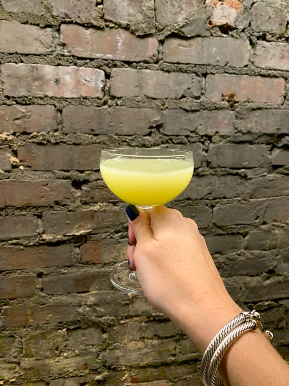 23 Awesome Things To Do in Durham - I'm Fixin' To - @imfixintoblog | Things to do in Durham by popular NC travel blog, I'm Fixin' To: image of a woman holding a yellow cocktail drink.