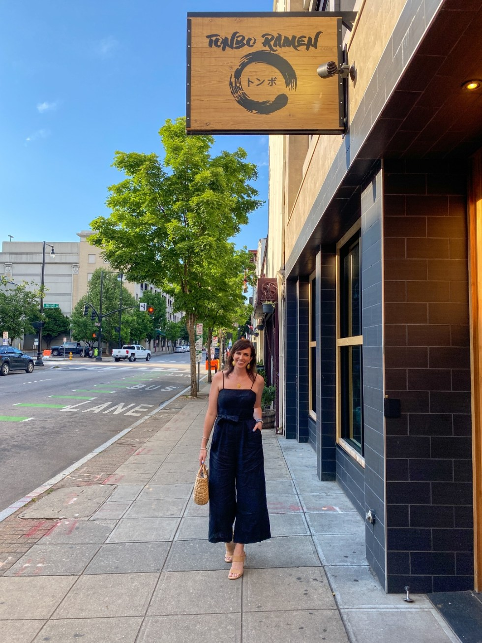 The Ultimate Girls' Day Out in Raleigh - I'm Fixin' To - @imfixintoblog | Girls Day Out In Raleigh by popular NC lifestyle blog, I'm Fixin' To: image of a woman wearing a black jumper and standing under a Tonbo Ramen sign.