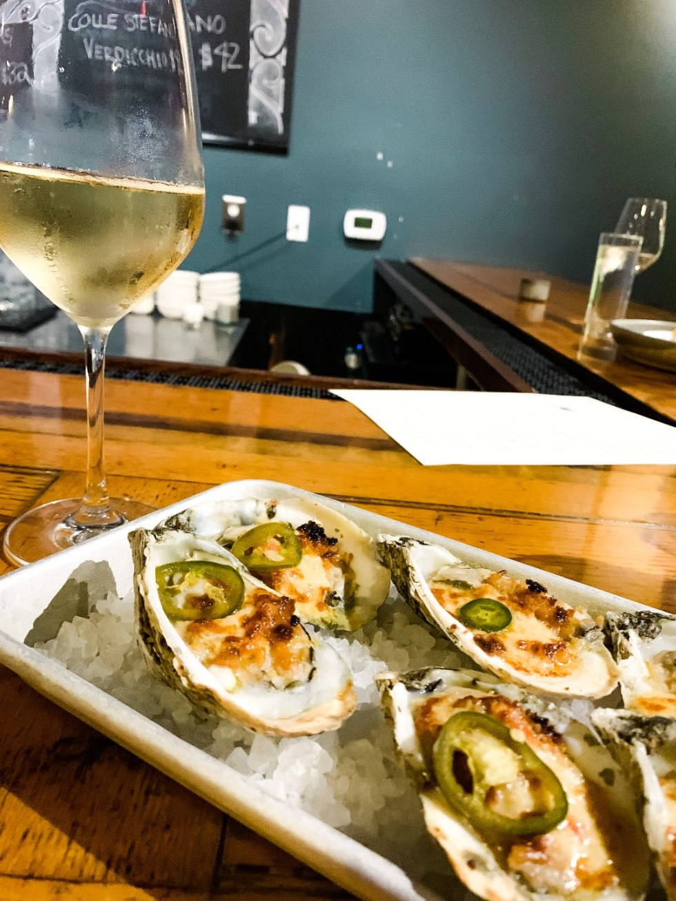 Raleigh Oyster Crawl - I'm Fixin' To - @mbg0112 | Raleigh Oyster Crawl by popular North Carolina blog, I'm Fixin' To: image of oysters on ice in a metal tray next to glass of white wine.