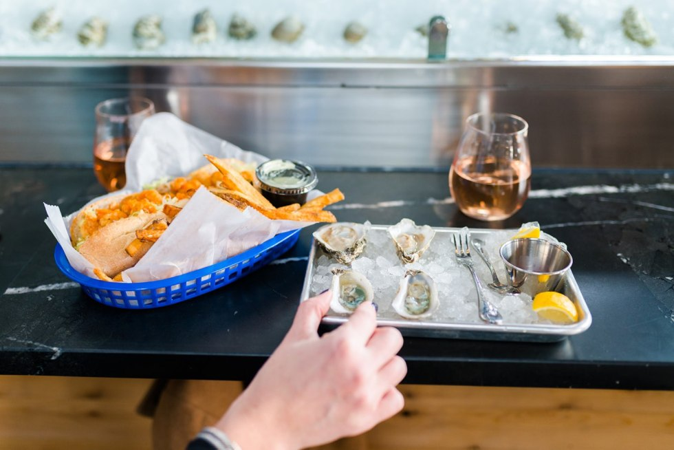 Raleigh Oyster Crawl - I'm Fixin' To - @mbg0112 | Raleigh Oyster Crawl by popular North Carolina blog, I'm Fixin' To: image of a tray of oysters on ice next to a blue plastic basket filled with a fried oyster sandwich and fries.