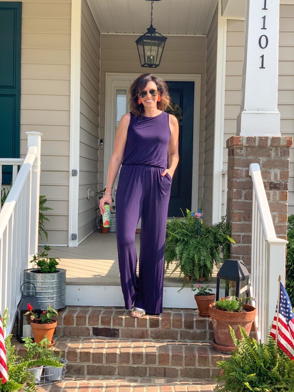 Welcome July + June Instagram Fashion Roundup by popular North Carolina life and style blog, I'm Fixin' To: image of a woman standing outside and wearing a purple Pink Lily Jumpsuit, J.Crew gold sandals, Mignonne Gavigan Mini Madelines, and Ray-Ban Original Aviator Polarized Sunglasses.