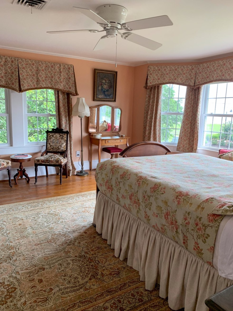 North Carolina Favorite: Between Water and Main Bed & Breakfast in Belhaven - I'm Fixin' To - @mbg0112 | North Carolina Favorite: Between Water and Main Bed & Breakfast in Belhaven by popular North Carolina Blogger, I'm Fixin' To: image of a peach and pink hued bedroom at Between Water and Main Bed and Breakfast.