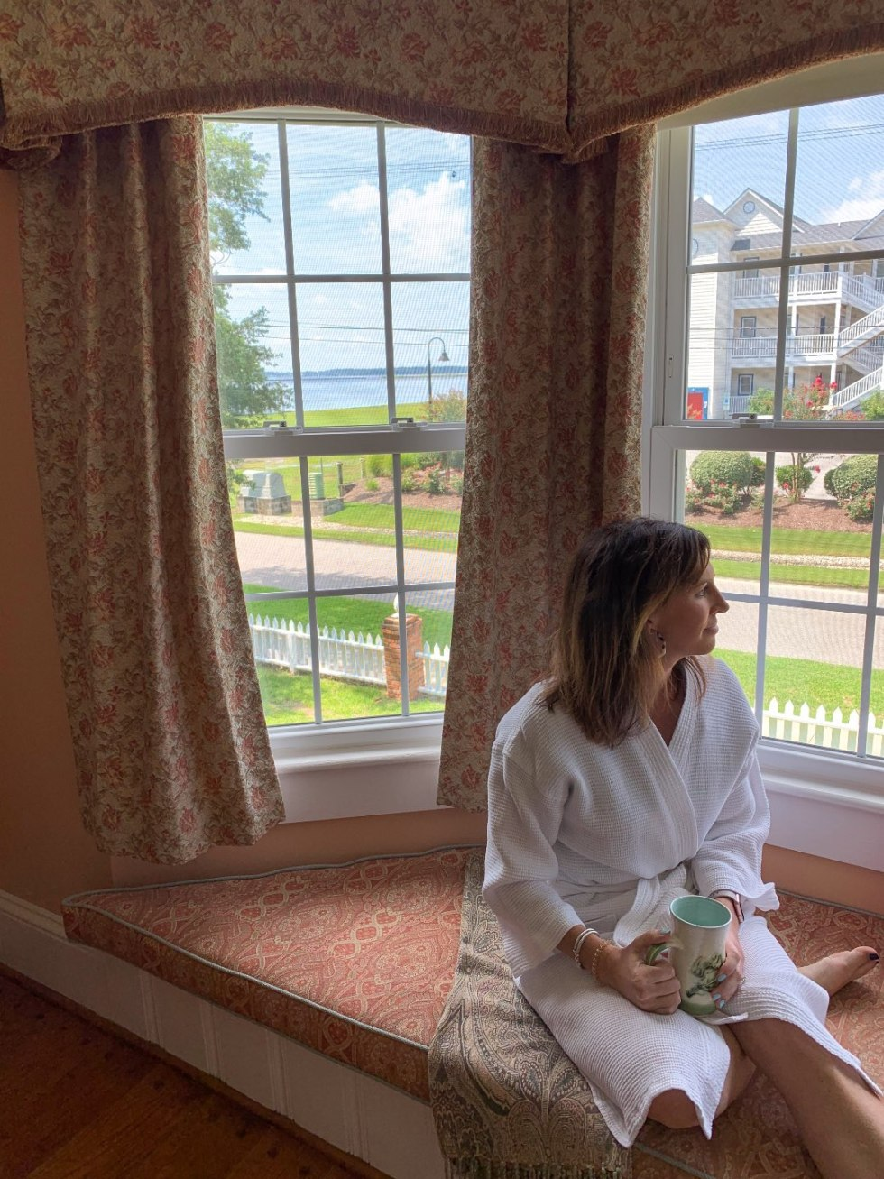 North Carolina Favorite: Between Water and Main Bed & Breakfast in Belhaven - I'm Fixin' To - @mbg0112   North Carolina Favorite: Between Water and Main Bed & Breakfast in Belhaven by popular North Carolina Blogger, I'm Fixin' To: image of a woman in a white robe sitting on a window bench and looking outside at Between Water and Main Bed and Breakfast.