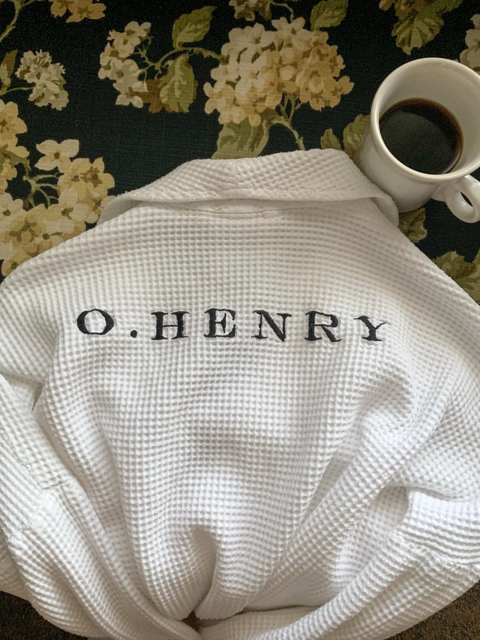 A Night at the O.Henry Hotel In Greensboro, NC - I'm Fixin' To - @mbg0112 | A Night at the O.Henry Hotel In Greensboro, NC by popular North Carolina blog, I'm fixin' To: image of the back of a white embroidered O. Henry Hotel hotel with a mug of coffee next to it.