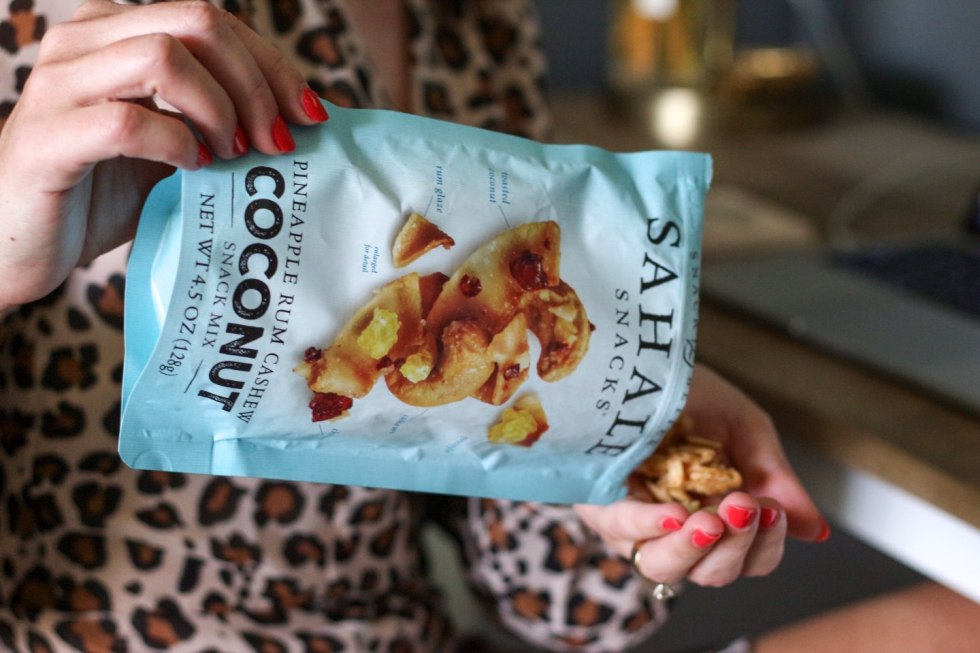 Quick Snack Ideas When You're On the Go by popular NC life and style blogger, I'm Fixin' To: image of a woman sitting at her computer desk and pouring a bag of Sahale Snacks coconut mix into her hands.