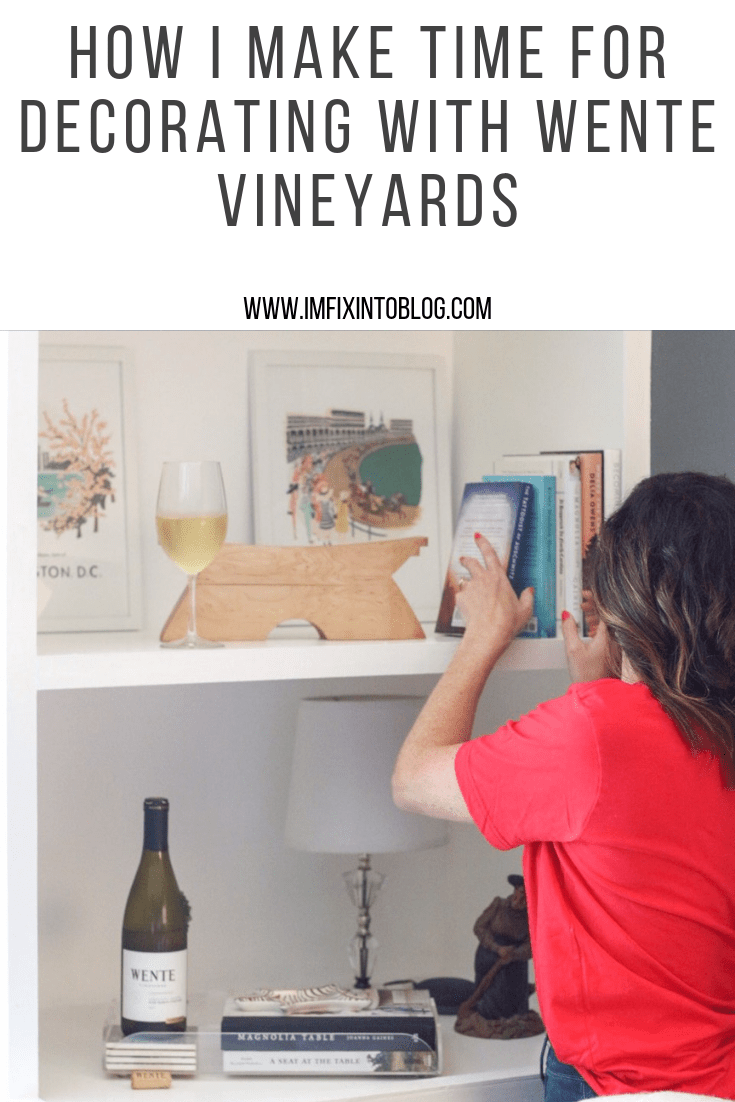 How I Make Time for Decorating with Wente Vineyards - I'm Fixin' To - @mbg0112 | How I Make Time for Decorating with Wente Vineyards by popular North Carolina lifestyle blog, I'm Fixin' To: Pinterest image of woman placing a book on her book shelf with a bottle and glass of Wente Vineyards wine on a book shelf next to a pile of books.