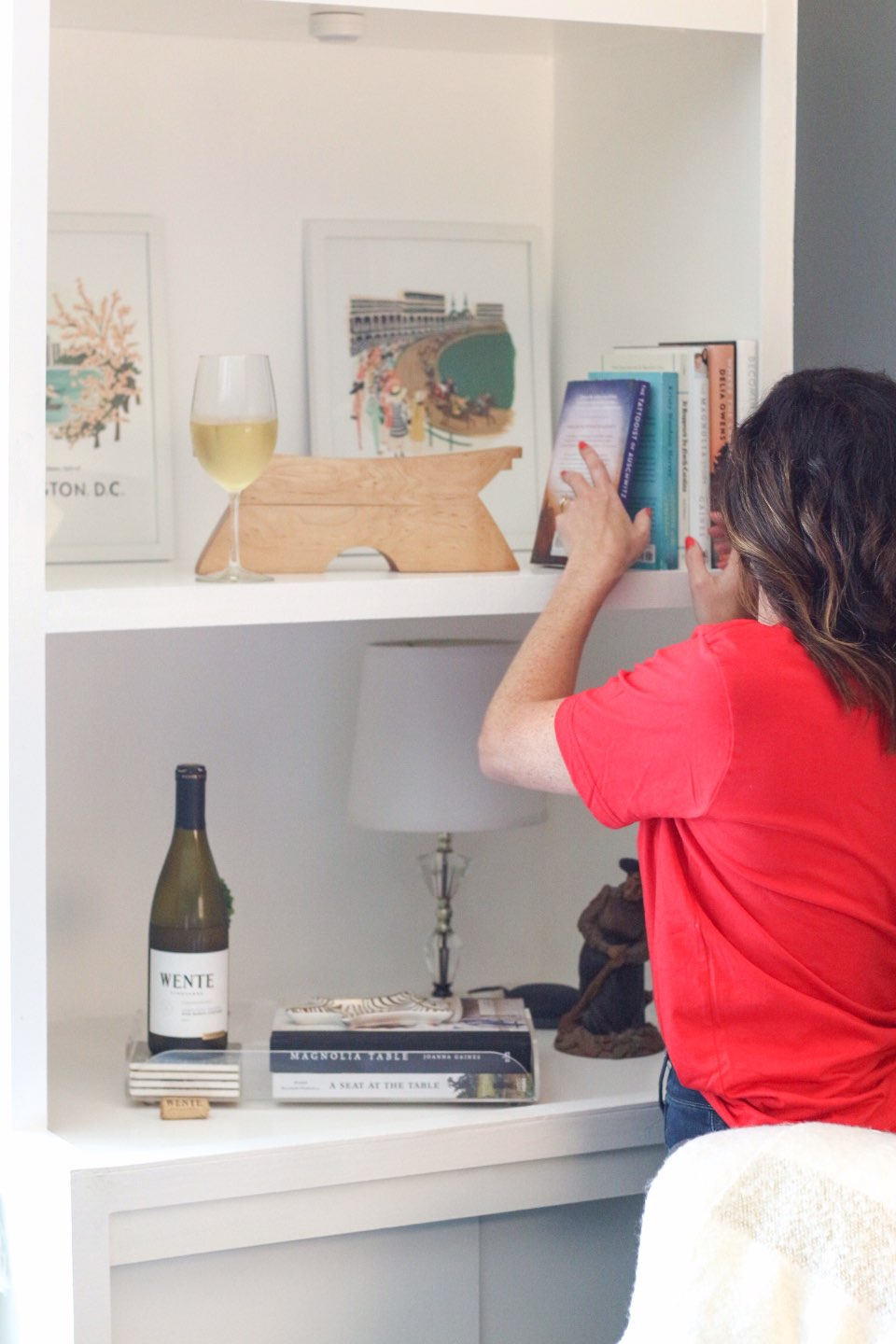 How I Make Time for Decorating with Wente Vineyards - I'm Fixin' To - @mbg0112 | How I Make Time for Decorating with Wente Vineyards by popular North Carolina lifestyle blog, I'm Fixin' To: image of a woman putting a book on a book shelf with a glass and bottle of Wente Vineyards wine next to her.