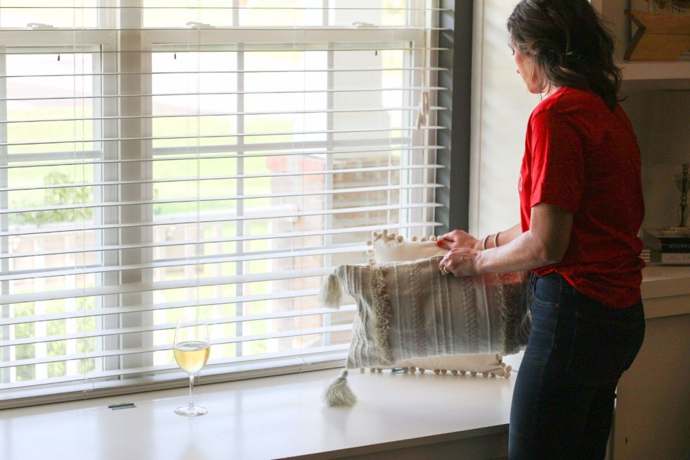 How I Make Time for Decorating with Wente Vineyards - I'm Fixin' To - @mbg0112 | How I Make Time for Decorating with Wente Vineyards by popular North Carolina lifestyle blog, I'm Fixin' To: image of a woman rearranging some throw pillows on her window bench with a glass of Wente Vineyards wine close by
