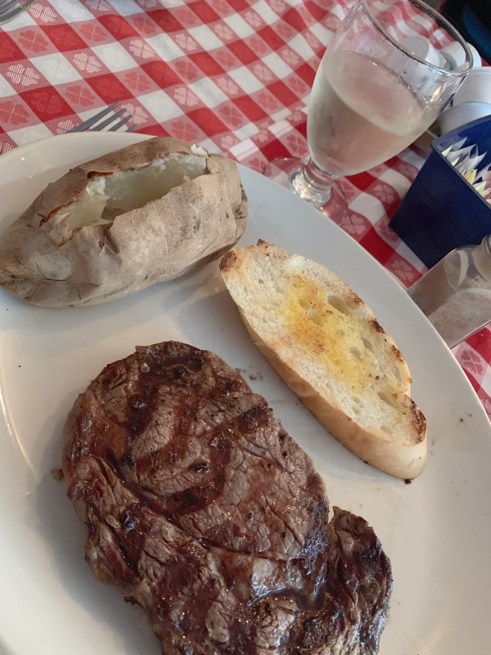 Top 5 Best Destination Restaurants in Eastern NC you Need to Try by popular North Carolina blog, I'm Fixin' To: image of steak, baked potato and bread at the Beefmastor Inn.