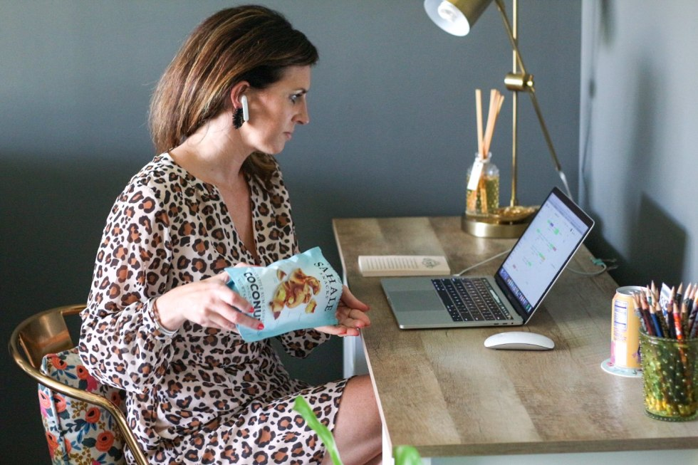 Quick Snack Ideas When You're On the Go - I'm Fixin' To - @mbg0112 | Quick Snack Ideas When You're On the Go by popular NC life and style blogger, I'm Fixin' To: image of a woman sitting at her computer desk and pouring a bag of Sahale Snacks coconut mix into her hands.
