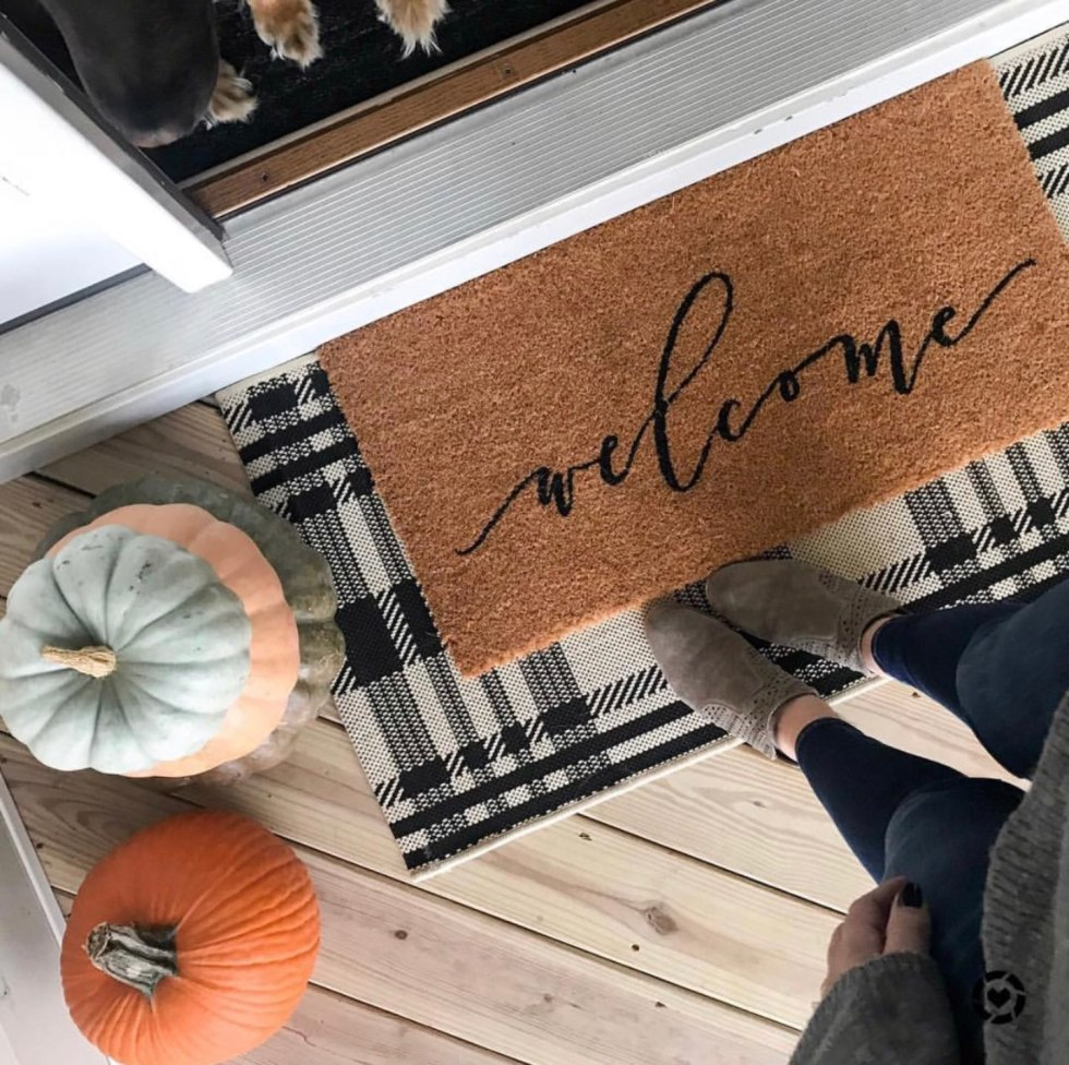 5 Layered Door Mat Combinations by popular North Carolina life and style blog, I'm Fixin' To: image of a woman standing on a layered door mat.